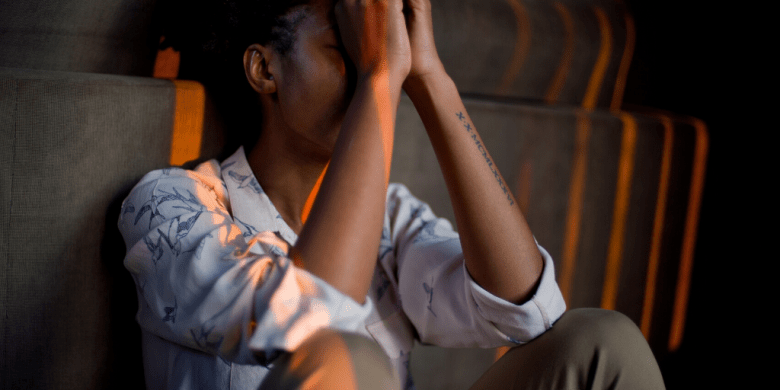 Social distancing can be hard on our mental health, but there are ways to keep ourselves going amid the struggle. Photo of stressed Black woman with hands in praying position in front of her face: Masimba Tinashe Madondo/Pixabay/Canva