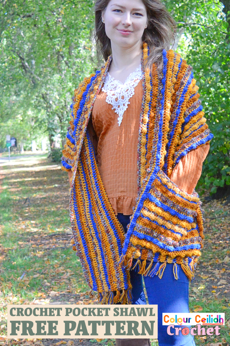 This crochet pocket shawl is called Autumn Berries and it is an easy breezy pattern with the tassel fringe made using the yarn tails from the color change. Featuring a generous size and a simple repeat of 5 colors, this relaxed style shawl is beginner friendly and is great for romantic walks in nature to snuggle yourself into. #crochetpocketshawl #crochet #pocketshawl
