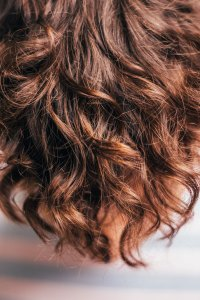 An image of wavy brown hair, representing the importance of a strand test