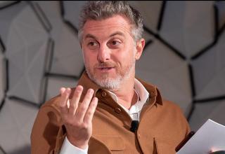 Homem branco de barba, ele gesticula como se estivesse falando algo. Está sentado, usa camisa em tons terrosos e em suas mãos segura alguns papéis. Luciano Huck