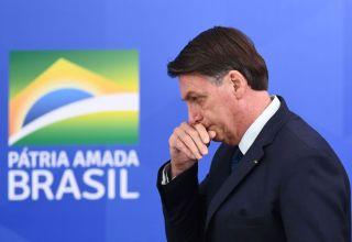 Bolsonaro com mão apoiada no nariz. Sembante de preocupado.
