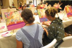 Students enjoying painting & wine class