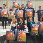 Happy customers show off paint and wine class paintings