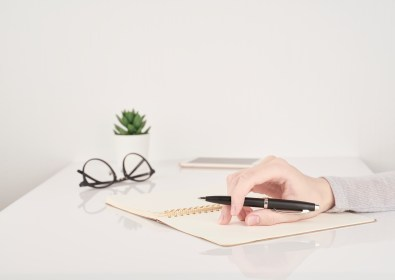 female young hand holding pen and writing on notebook page on white and gray background side view copy space