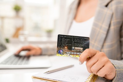 Yellow credit card with black magnet line held by young contemporary businesswoman over page of notebook during work