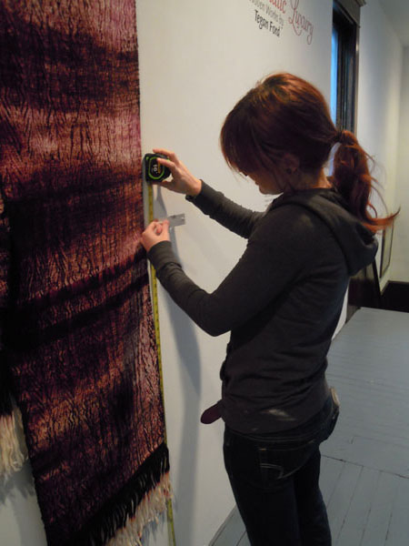 "Myself, hanging my artwork for my Senior Exhibition ""Chromatic Luxury: Woven Works by Tegan Ford"" in 2011."