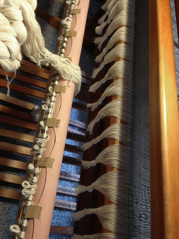 The blankets were cut off and the old warp threads were bundled into groups to prevent from slipping back through the reed.