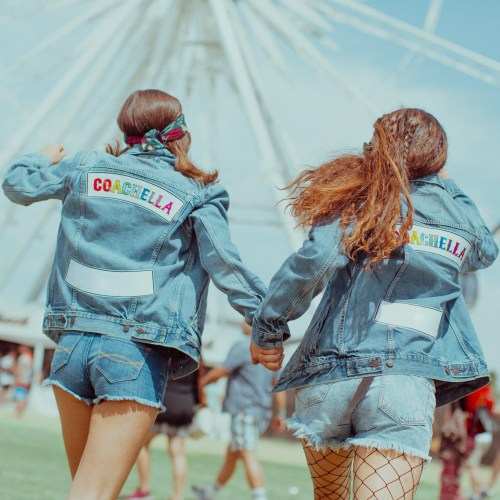Two girls wearing Coachella denim jackets at Coachella music festival