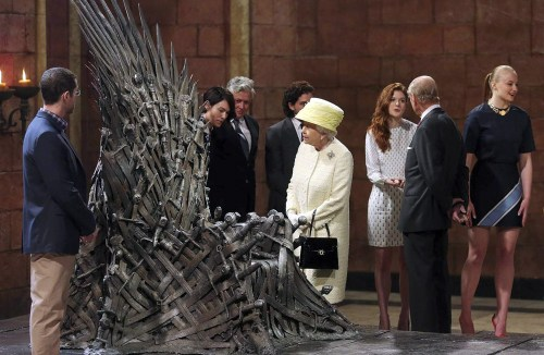 While Queen Elizabeth examines the Iron Throne, Prince Philip greets Thrones cast members (from right) Sophie Turner (Sansa), Rose Leslie (Ygritte), Kit Harington (Jon Snow), Conleth Hill (Varys), and Lena Headey (Cersei). To the left of the Throne is series co-creator D.B. Weiss.