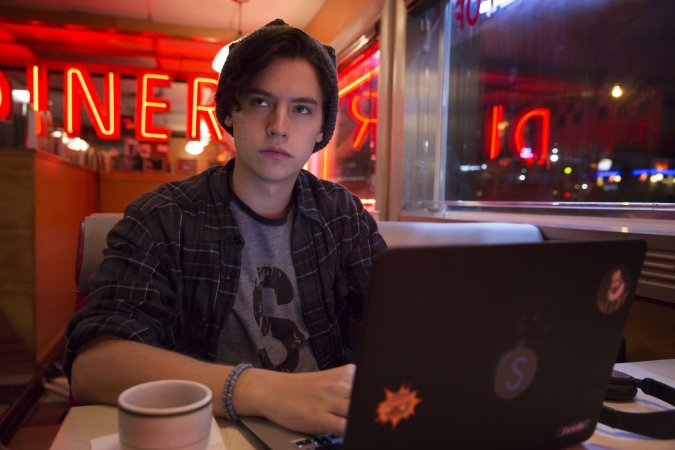Jughead (Cole Sprouse) writing in the diner