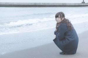 砂浜でいじける女性