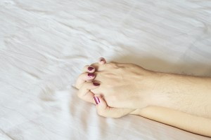 Man holding woman hand on white bed, couple sexual concept