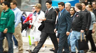 business men walking across road talking
