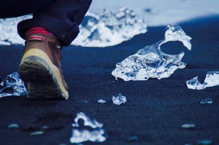 Bloc de glace échoué sur la plage de sable noir