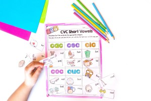 Child using short vowels phonics worksheet by gluing cutouts onto the worksheet