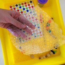 Hand holding bubble wrap with stickers, playdoh, and beads in a tub underneath the bubble wrap.