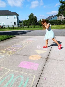 A little girl with a blue dress and brown shoes is preventing the summer slide by home learning on an obstacle course drawn from chalk