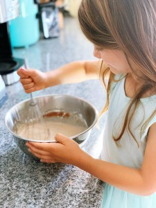 A little girl with brown hair and a blue dress is stirring cake mix with a whisk as she is helping her parents cook while learning math
