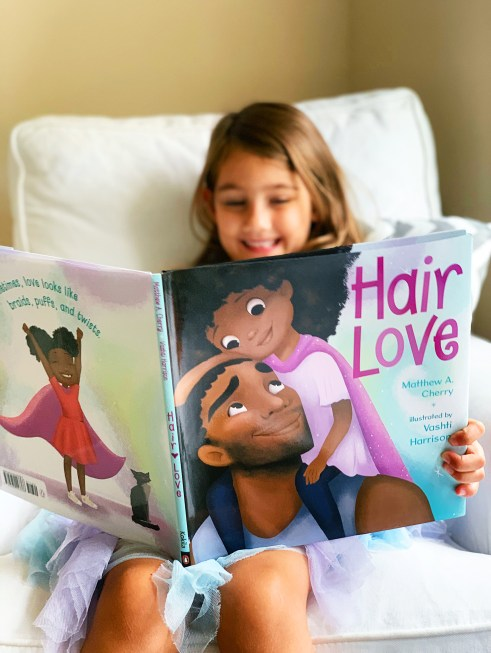 Girl reading Hair Love mentor text