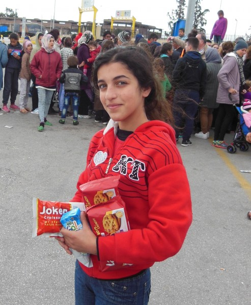 In the background, Arabic-speaking refugees vie for snacks tossed from a van by an informal network of Samaritans from central Athens. This girl, who spoke no English, scored her cookies and juice box early, and insisted on documenting her success in a photo. March 18, 2016