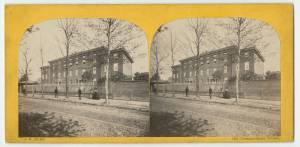 Picture shows two almost identical photographs on a cardboard mount. Photographs show the exterior of the multi-story, half block long brick building of the Pennsylvania Institution for the Instruction of the Blind. Building contains many rectangular-shaped windows. A tall picket fence lines the property. Three men and two women stand on the sidewalk evenly lined with trees in front of the fence. The men stand a few feet apart from each other and the women stand next to each other a few feet to the right of the men. The men wear dark-colored hats and suits. The women are attired in dark-colored hats and one is in a light-colored, long-sleeved dress with crinoline skirt, and the other in a dark-colored, long-sleeved dress with crinoline skirt. [End of description]