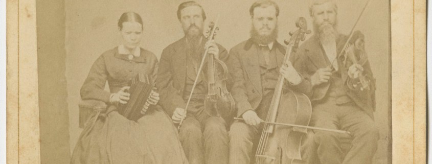 [Portrait of Hostetler family of blind musicians]. Mount Pleasant, Penna.: From A. N. Staufer, [ca. 1866]. Black & white photograph. 4 x 2.5 in. Picture shows one woman and three men, seated next to each other, and holding instruments. The woman holds an accordion in her lap and she looks slightly down. To her left is a man, his eyes closed, who holds a viola perpendicular to his lap with one hand and a bow in his other. To his left is a man resting a cello between his legs. He holds a bow across the base of the cello with his right hand. To his left is the last man, his eyes closed, who holds a violin by his left shoulder and a raised bow in in his right hand. The woman, as well as the man who holds a cello, wear glasses. The woman wears a dark-colored corseted dress with long sleeves and a long skirt. The men, who look toward the viewer, are bearded and wear dark-colored suits. [End of description]]