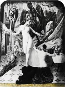 Picture depicts a composition inspired by folk-art devotional paintings known as retablo. Picture shows two nude female models, painted white to resemble sculpture, and staged on a pedestal covered in flowing drapery. To the viewer's left stands a woman, her light colored hair pulled back into a low bun, her shoulders slightly pulled back and her arms stretched out from her sides. Her right leg is bent back and up toward her buttocks. She holds an upright sword in her right hand. She gazes down, to the viewer's right, at a seated nude female figure with shortened arms and legs. Her back is to the viewer. Her dark wavy hair is pulled back into a low bun, and her left arm reaches to the standing figure. Her right arm rests on a small table covered with a white cloth. A vase of flowers adorns the table. The figures are in front of an elaborate backdrop. In the far left is a large nude photograph of the forward standing model. In the photo, she is standing with her left arm curved above her head and her right arm bowed down past her waist. Her right hand touches her inner left thigh. In the far right, next to the photograph, is a painted, shadowed, and winged form looking at a hand of salvation. A skeleton model lounges on the far left side of the scene. He is partially covered in drapery. He looks toward the women. The flooring extending from the front to the back of the scene is decorated with fleur-de-lis like details. Three lines of writing – the Retablo prayer – adorn the lower edge of the photograph on an attached yellow strip of paper. [end of description]