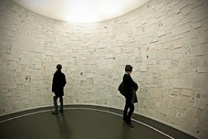 Picture shows two people, a man and a woman, on the side of a circular room farthest from the viewer. The man wears a winter coat and the woman has hers swung over her arm. They stand a few feet apart from each other. The curved wall, in front of them, is covered from floor to ceiling in pieces of paper. The papers have writings on them. [end of description]