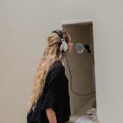 Picture shows a woman standing in front of a niche in a wall. She wears a headset, its cord extending from within the nice. Her face is near a funnel at the end of a mic-like stand. She wears a black shirt and pants, and has her long blond hair pulled slightly away from her face.