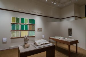 Picture shows the gallery, including four of Jaynes's seven installations on view. In the center foreground is Jaynes's Gift#1 on display on a flat, horizontally-angled rectangular table with a dark wood base. A white and brown paper owl rests on a cylindrical stand to the left of a large open book under a rectangular, clear acrylic hood. To the right of the display with the owl stands Jayne's Gift #5, a map representation of the travels the 19th–century blind surveyor John Metcalf. It is a vertically-positioned, large rectangular table composed of a a linen top and a light brown wood base. A multi-color grid, outlines of geometric shapes, and green porcelain geometric shapes adorn the linen top. In the center background, on the back wall painted off-white, is Jayne's Gift #4, a visual transmutation after the musical work of blind African American musician Thomas Wiggins. It is three horizontal and three vertical rows of prints in a geometric interplay of greens, browns and yellows. To the right of the prints on the wall is a small wooden frame in which brass musical notes are displayed. To the far right background is a view of Jaynes's Gift #6, the scent mechanism the olfactometer, in a niche in an off-white curved wall. The floor of the room is covered with a tan colored carpet.