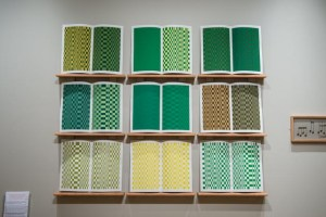 Picture shows the installation, which consists of nine screen prints across facing pages. They are displayed on wall mounted wooden shelves, spaced apart, in 3 vertical and 3 horizontal rows. The prints embody a visual translation of Wiggins's music in a geometric interplay of greens, browns and yellows. Partially visible to the left is a wooden frame containing brass musical notes.