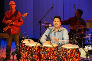 Picture shows Pablo Batista at his four-piece drum set during the middle of a concert. Batista has his eyes closed and his hands flutter above the drum in front of him. He wears a blue long sleeve shirt with dark blue ornamental details at the shoulders. A fellow musician with a guitar strapped over his shoulder stands to Batista's right. Another drummer, seated at his drum set, plays behind Batista. [end of description]