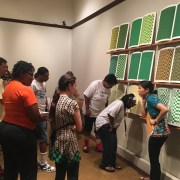 Photo shows a large group of individuals gathered in front of Teresa Jaynes's Gift #4 of nine green, yellow, and brown screen prints. The screen prints depict grid patterns. In the right of the image, a young woman attired in black pants and a short-sleeved teal blouse with a flower pattern on the edge, slightly hunches over as if listening to something. Her right hand is to her ear and her left hand holds a large envelope to her waist. To her left, are two women. They lean and bend over in listening stances. In the left of the image, is a group of men and women in summer clothes. They look toward the women standing in front of the screen prints. The screen prints are hung above a short white-colored floor riser. [end of description]