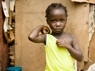 Africa Regional Review - An African girl sitting outside her house in a torn yellow vest.