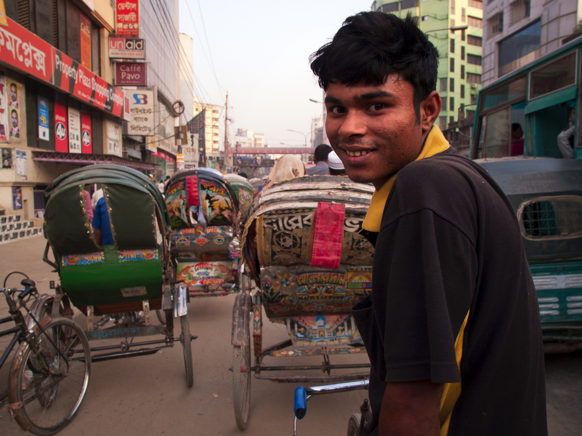 Young Rickshaw driver patiently wait on the vehicle during traffic jam. World Bank to Help Bangladesh