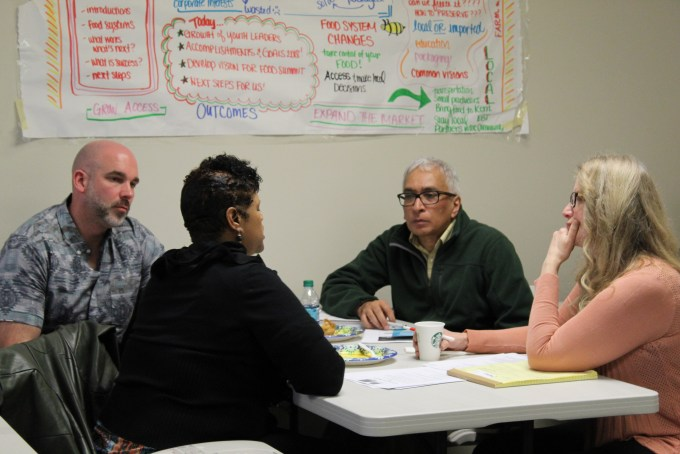 Four people meeting for small group discussion at workshop