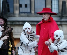 The Cardinal grasped by the skeleton dancers. Photo credit: Susan Dew.