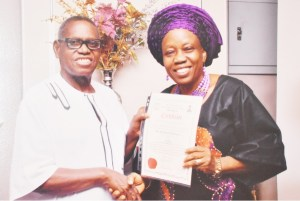 The Deputy Director of Centre for Entrepreneurial Studies (CENTS), Dr, Elizabeth Oluwalana displaying her Award of Fellow of Institute of Management Consultants (IMC) amid warm handshake by the Director General of IMC, Professor David Lornem