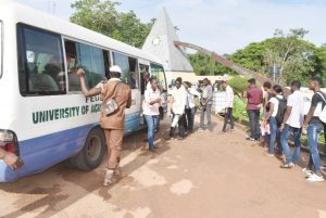 A stretch of candidates on queue boarding FUNAABOT Bus to Post-UTME Screening Centres