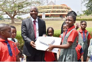 A Pupil of Dew Hills Primary School Making a presentation of school to the representative of the Vice-Chancellor, and Deputy Vice-Chancellor (Development), Professor Lateef Sanni.
