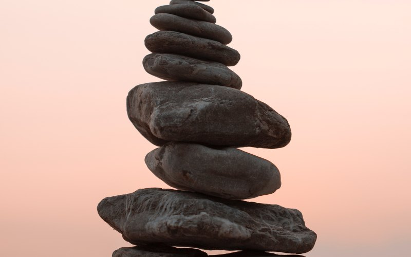 grey stones balancing on top of each other against a pale orange sky