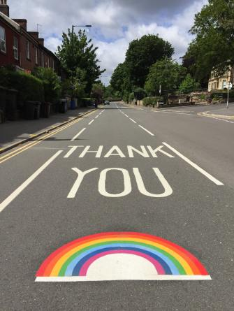 thank you written on a road with a rainbow