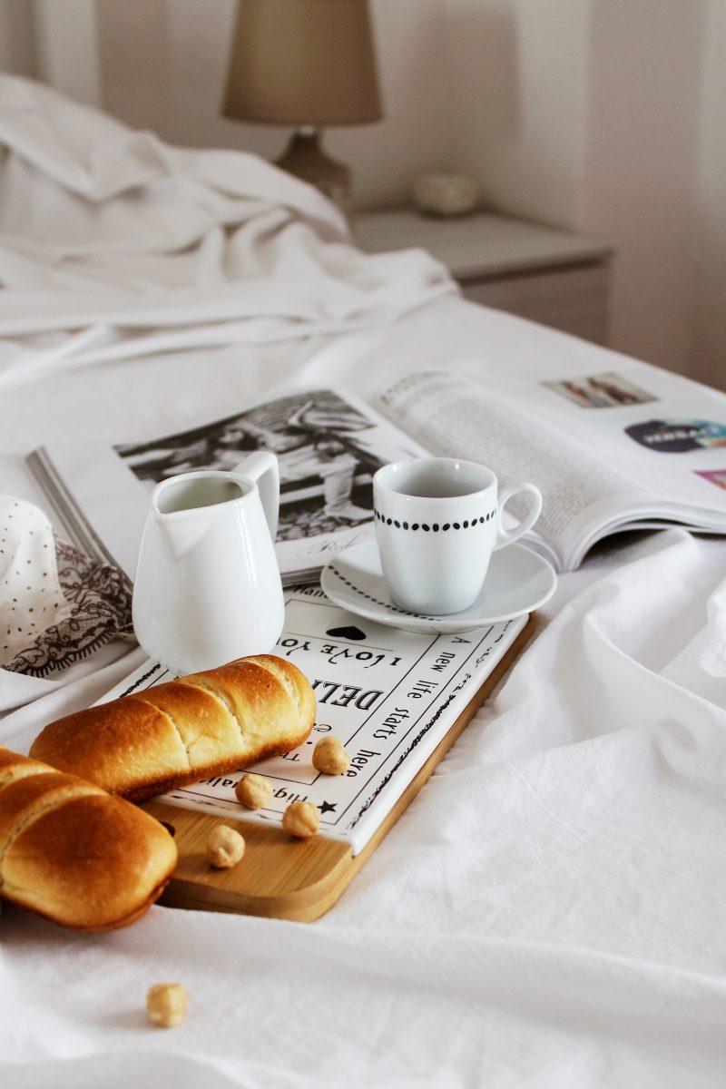 bread on white ceramic plate beside white ceramic mug on brown wooden tray
