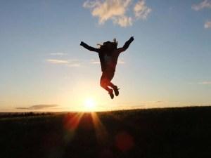 girl jumping sunset