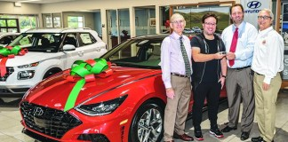Justin Dash, chair of the 49th annual Miami International Auto Show (second from right), presents Steven Cruz (second from left) with the key to a 2020 Hyundai Sonata SEL Plus. Also sharing in the presentation are William Lehman Jr. of the South Florida Automobile Dealers Association (left) and Cliff Ray, auto show coordinator of the Auto Show (right).