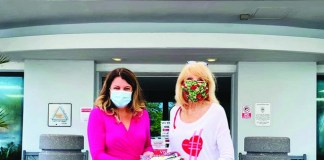 Coral Gables Hospital staff try on recently donated masks sewn on behalf of GFWC Coral Gables Woman's Club to thank front-line workers. Pictured with the new masks are Tenet's Patty Vila and CGWC board member Gloria Burns, a former long time Pinecrest resident.