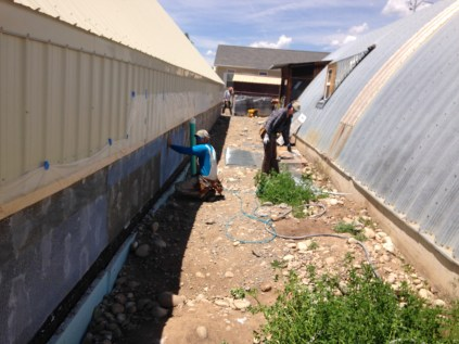 Down the north side of the greenhouse, we apply a lime / sand plaster to the exterior.