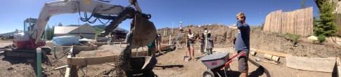Interns Matt, Sarah, Mike, and Laura watch the next gravel pour into our wheelbarrow.