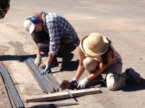 Interns Beatrice and Stacey measure and cut rebar with a handheld grinding wheel.