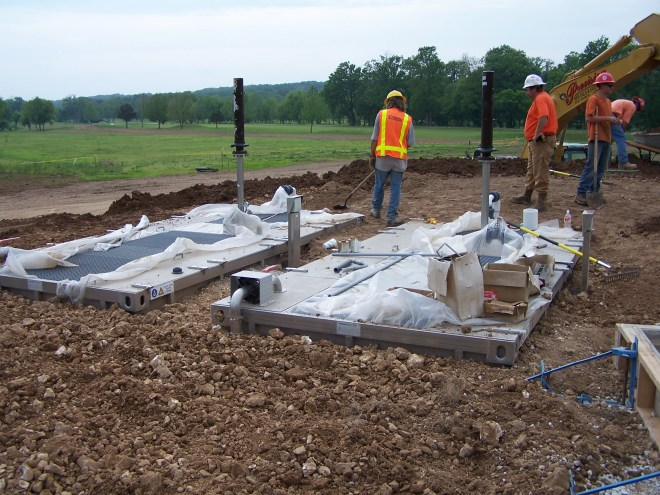 men bringing landscape up to grade around two package wastewater treatment plants